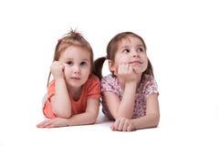 Små flickor som ligger på golvet royaltyfri bild
