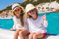 Små flickor som seglar på fartyget i det klara öppna havet Arkivbild