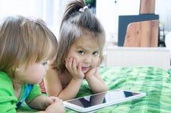 Små flickor som ser på blocket som ligger på säng Barntidutgifter Ungar som använder minnestavladatoren arkivbild
