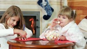 Små flickor som skrivar brev till Santa Claus, closeupstående, söta drömmar, magisk jultid stock video
