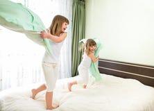 Små flickor som slåss med kuddar i sovrum royaltyfria foton