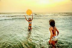 Små flickor som spelar med bollen i havet royaltyfri bild