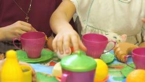 Små flickor som spelar med plast- bordsservis stock video