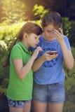 Små flickor som spelar med telefonen royaltyfri foto