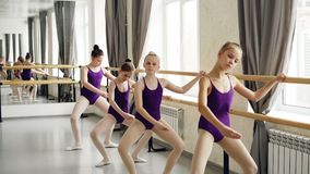 Små flickor som startar balettdansörer i body, gör övningar som rymmer praktiserande olika positioner för balettstång stock video