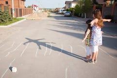 Små flickor som tillsammans hemma spelar yttersidan på en sommardag Arkivfoton