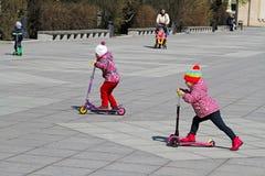 Små flickor som utomhus rider sparkcyklar i parkera Gorkogo Royaltyfri Bild