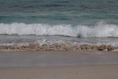 Små fridsamma vågor som bär sand arkivbilder