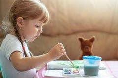 Små fyra år gammal caucasian flickafärgläggningbild vid målarfärgsammanträde på tabellen, barns utveckling arkivbild