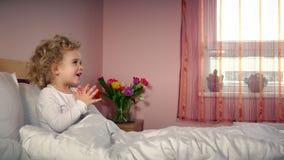 Små gladlynta händer för barnflickaapplåd och får gåvan den närvarande asken på säng stock video