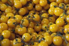 Små gula tomater som säljs på marknaden arkivfoton