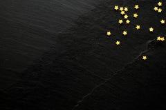 Små guld- sockerstjärnor på svart bakgrund med utrymme för ditt meddelande Royaltyfri Foto