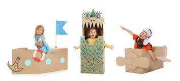Små gulliga barn som spelar med kartonger på vit Handgjord leksaker och dräkt royaltyfria bilder