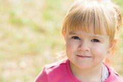 Små gulliga flickaleenden och blickar in i kameran i en stad parkerar royaltyfri foto