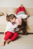 Små gulliga flickor på den uppochnervända soffan Fotografering för Bildbyråer