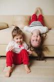 Små gulliga flickor på den uppochnervända soffan Arkivfoto