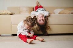 Små gulliga flickor på den uppochnervända soffan Royaltyfria Foton