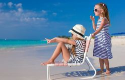 Små gulliga flickor på den vita stranden under semester Fotografering för Bildbyråer