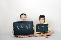 Små gulliga flickor rymmer ett bräde med ordfamiljen Royaltyfri Fotografi