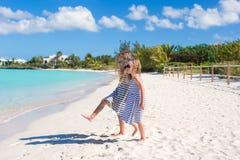 Små gulliga flickor som promenerar den vita stranden Fotografering för Bildbyråer