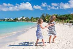 Små gulliga flickor som promenerar den vita stranden Arkivbild