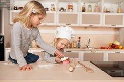 Små gulliga flickor som smakar kakan i kök Arkivfoto