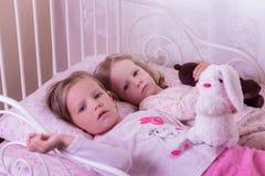 Små gulliga flickor (systrar) spelar i säng Arkivbilder