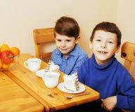 Små gulliga pojkar som äter efterrätten på träkök planlagd strömförande retro lokalstil för hemmiljö Royaltyfri Bild