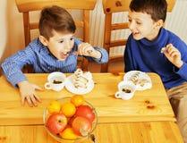 Små gulliga pojkar som äter efterrätten på träkök planlagd strömförande retro lokalstil för hemmiljö Royaltyfri Foto