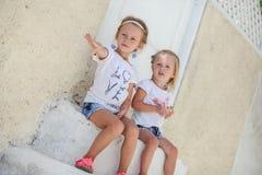 Små gulliga systrar som in sitter nära gammalt hus Arkivbild