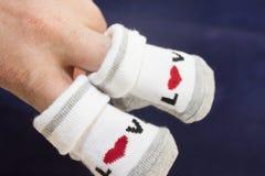 Små händer som rymmer, behandla som ett barn sockor arkivbild