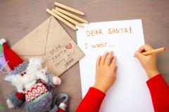 Små händer som skrivar ett brev till jultomten flatlay royaltyfria bilder