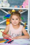 Små härliga flickaattraktioner i färgrika blyertspennor arkivbilder