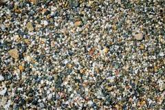 Små havsstenar på kusten som täckas med en havsvåg Royaltyfria Foton