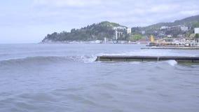 Små havsvågor med skumavbrottet på vågbrytaren Semesterortstad för flyg- sikt, berg i bakgrund Strands?song Landskap f?r havskust lager videofilmer