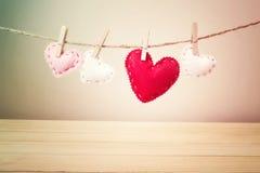 Små hjärtor med häftklammer som hänger på en rad Arkivbilder