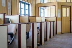 Små individuella kabiner med datorer och stolar i ett kontor arkivfoto
