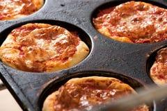 Små individuella pizza i en bakplåt Fotografering för Bildbyråer