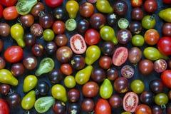 Små körsbärsröda tomater, olika färger: rött gult, grönt, bla Arkivbild