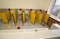 Små kabiner med litet vatten i grundskola för barn mellan 5 och 11 år med en stor whit Fotografering för Bildbyråer