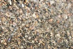 Små kiselstenkiselstenar under bakgrunden för vattenyttersidafoto royaltyfri bild