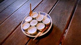 Små kokosnötpuddingkoppar i runt keramiskt magasin arkivbild