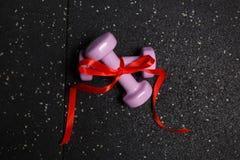 Små konditionhantlar på en svart bakgrund av golvet Royaltyfri Foto