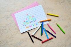 Små kulöra blyertspennor & en teckning Arkivbild