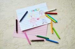 Små kulöra blyertspennor & en teckning Arkivfoto