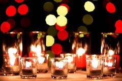 Små lampor i små exponeringsglas med en suddighet stora röda stearinljus in Arkivfoto