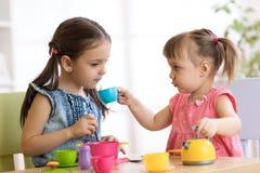 Små lyckliga barn, det gulliga lilla barnet och ungeflickor spelar med plast- leksakkök inomhus hemma eller dagiset royaltyfri bild