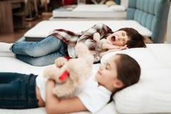 Små lyckliga flickakramar uthärdar att ligga på säng I bakgrundspyssömnar royaltyfri bild