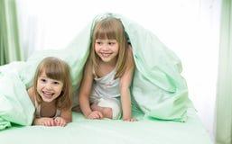 Små lyckliga flickor som ligger under filten på säng Arkivbild