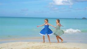 Små lyckliga roliga flickor har mycket gyckel på den tropiska stranden som tillsammans spelar långsam rörelse arkivfilmer
